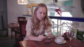 La mujer está mirando en el smartphone que se sienta en un restaurante almacen de metraje de vídeo