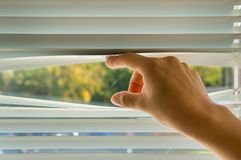 La mujer está mirando hacia fuera a través de persiana imagen de archivo libre de regalías