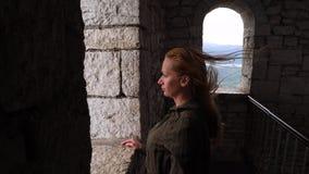 La mujer está mirando hacia fuera la ventana de la torre el viento sopla en su pelo 4k, cámara lenta almacen de metraje de vídeo