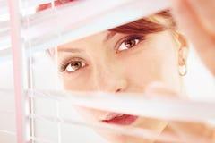La mujer está mirando a través de la persiana SM Fotos de archivo libres de regalías
