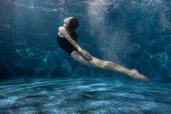 La mujer está nadando en la parte inferior de la piscina Imagen de archivo
