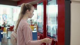 La mujer está ordenando por la máquina automática electrónica en restaurante de los alimentos de preparación rápida almacen de video