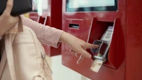 La mujer está pagando por la tarjeta en el autómata, primer de manos metrajes
