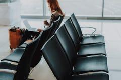 La mujer está pasando tiempo con el ordenador portátil en el aeropuerto fotos de archivo libres de regalías