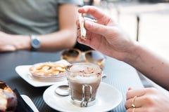La mujer está poniendo el azúcar marrón en su bebida Fotografía de archivo