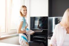 La mujer está poniendo las galletas en el horno, que su madre e hija hicieron Ella los mira Foto de archivo libre de regalías