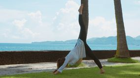 La mujer está practicando la yoga, ejercicio en actitud de la montaña y está estirando la pierna para arriba, en la playa, el fon almacen de metraje de vídeo