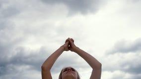 La mujer está practicando la yoga en nubes del fondo - fabricación del namaste de saludo de la mano almacen de video