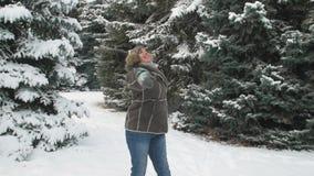 La mujer está presentando en el bosque del invierno, paisaje hermoso con los abetos nevosos almacen de metraje de vídeo