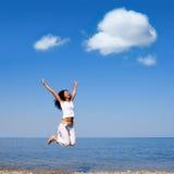 La mujer está saltando en la playa Foto de archivo libre de regalías