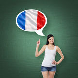 La mujer está señalando la burbuja del pensamiento con la bandera francesa Fondo verde de tablero de tiza Imagenes de archivo