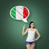 La mujer está señalando la burbuja del pensamiento con la bandera italiana Fondo verde de tablero de tiza Fotos de archivo