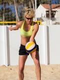 La mujer está sirviendo el voleibol de playa Fotos de archivo libres de regalías