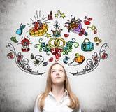 La mujer está soñando sobre absorber Los iconos coloridos de las compras se dibujan en la pared Fondo concreto Imagen de archivo