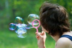 La mujer está soplando burbujas de jabón Imagen de archivo libre de regalías