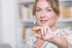 La mujer está sosteniendo la jeringuilla con la insulina o la heparina imágenes de archivo libres de regalías