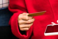 La mujer está sosteniendo la tarjeta de crédito para las compras en línea para el regalo del Año Nuevo de la familia Imagen de archivo