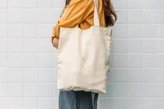 La mujer está sosteniendo la tela de la lona del bolso para la plantilla del espacio en blanco de la maqueta fotos de archivo