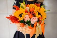 La mujer está sosteniendo un ramo anaranjado brillante y colorido de flores Fotografía de archivo