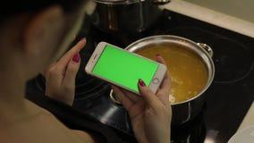 La mujer está sosteniendo un smartphone con una pantalla verde, y está cocinando la sopa almacen de video