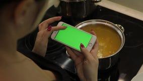 La mujer está sosteniendo un smartphone con una pantalla verde, y está cocinando la sopa metrajes