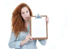 La mujer está sosteniendo un tablero Un adolescente redheaded tiene hai rizado Fotos de archivo