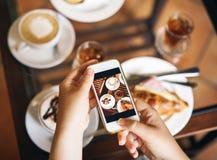 La mujer está sosteniendo un teléfono Desayuno para dos: un cruasán con el jamón, café Imagen de archivo