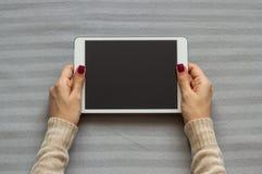 La mujer está sosteniendo una tableta, mintiendo en una manta suave fotografía de archivo libre de regalías