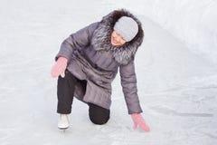 La mujer está subiendo después de la caída en una pista Imágenes de archivo libres de regalías