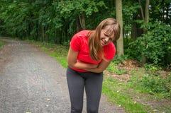 La mujer está teniendo dolor abdominal durante actividad corriente Imagen de archivo libre de regalías