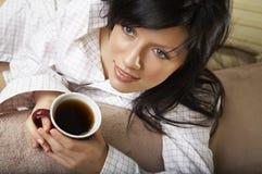 La mujer está teniendo su té de la mañana Foto de archivo libre de regalías