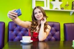 La mujer está tomando el selfie en un café Imagen de archivo