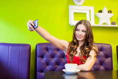 La mujer está tomando el selfie en un café Fotografía de archivo libre de regalías