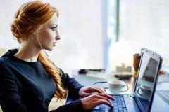 La mujer está trabajando en el ordenador portátil en el café Fotografía de archivo
