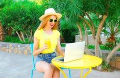 La mujer está trabajando usando un ordenador portátil se sienta en un café Imagen de archivo