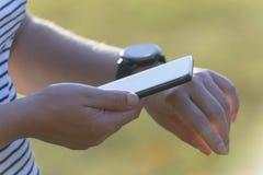 La mujer está utilizando el smartwatch y el teléfono elegante fotografía de archivo libre de regalías