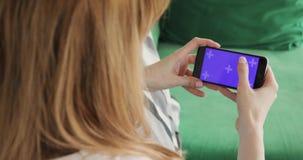 La mujer está utilizando el teléfono móvil con la pantalla horizontal púrpura dominante de la croma, el teléfono y el primer de l almacen de metraje de vídeo