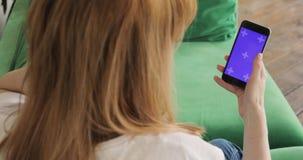 La mujer está utilizando el teléfono móvil con la pantalla vertical púrpura dominante de la croma, el teléfono y el primer de las metrajes