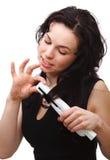 La mujer está utilizando a la enderezadora del pelo Fotografía de archivo libre de regalías