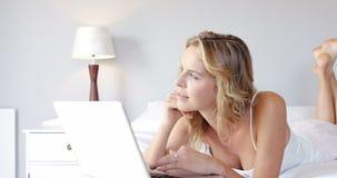 La mujer está utilizando un ordenador portátil metrajes