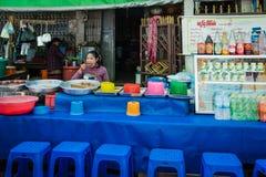 La mujer está vendiendo y está comiendo Foto de archivo libre de regalías