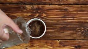 La mujer está vertiendo el agua hirvienda para ahuecar con el café instantáneo, cámara lenta metrajes