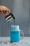 La mujer está vertiendo el café en taza de leche azul coloreada en un fondo blanco y negro Batido de leche, cocktaill, frappuccin Foto de archivo