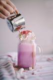 La mujer está vertiendo el café en taza de leche coloreada con crema, la melcocha y la decoración colorida Batido de leche, cockt Fotos de archivo libres de regalías