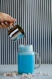 La mujer está vertiendo el café en taza estilizada del tarro de albañil de leche azul coloreada en un fondo blanco y negro Batido Fotografía de archivo