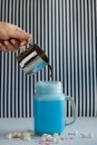 La mujer está vertiendo el café en taza estilizada del tarro de albañil de leche azul coloreada en un fondo blanco y negro Batido Foto de archivo libre de regalías