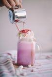 La mujer está vertiendo el café en taza estilizada del tarro de albañil de leche coloreada con crema, la melcocha y la decoración Fotografía de archivo