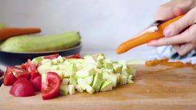 La mujer est? cocinando Las manos de las mujeres cortaron verduras en una tabla de cortar metrajes