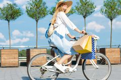 La mujer est? completando un ciclo en vestido azul en la bicicleta blanca con la cesta de flores foto de archivo