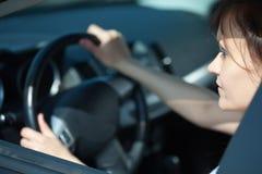 La mujer está conduciendo su coche Imágenes de archivo libres de regalías